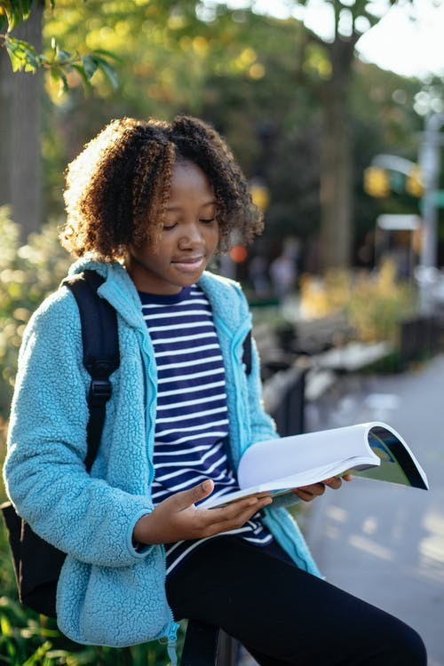African American schoolchild in casual apparel with rucksack watching exercise book in town in back lit