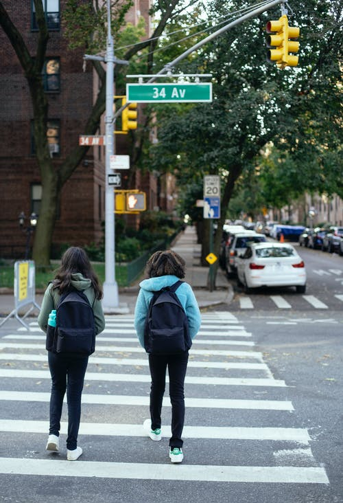 Unrecognizable schoolgirls with backpacks crossing city road