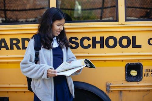 Charming ethnic schoolgirl watching exercise book on street