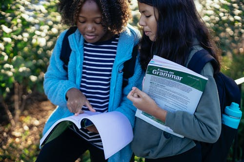 Crop black schoolchild pointing at exercise book while talking to ethnic girlfriend in sunlight