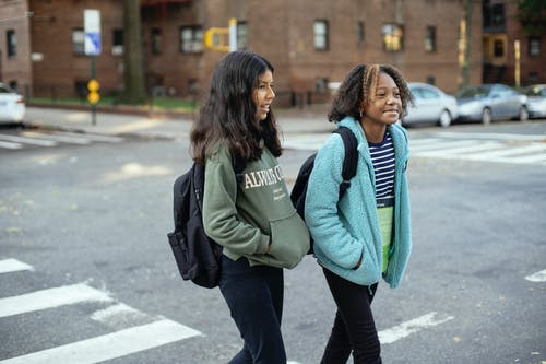 Content multiracial girlfriends with school bags and hands in pockets interacting on urban crosswalk while looking away