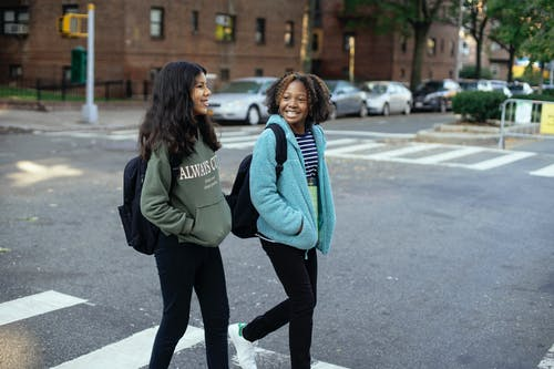 Happy multiethnic girlfriends with backpacks speaking on city road