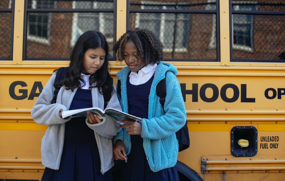 Multiethnic schoolchildren in uniforms watching exercise book near yellow school bus reflecting building in town