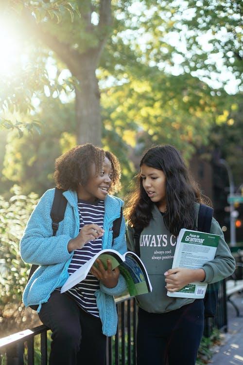 Cheerful diverse schoolgirls with workbooks talking on street
