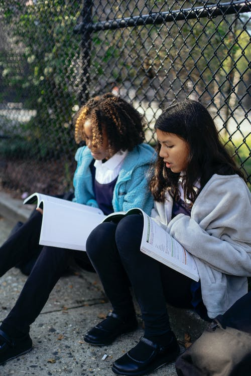 Multiracial schoolchildren with exercise books interacting near street grid fence