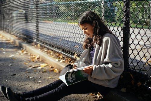 Ethnic schoolgirl with workbook doing homework on city street