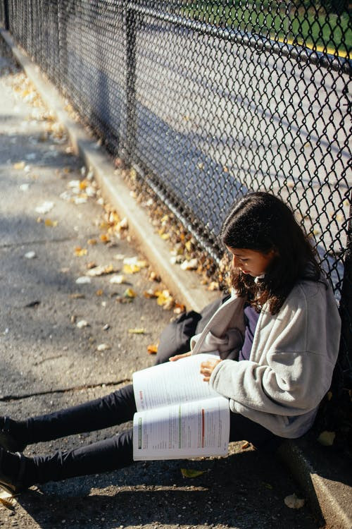 From above of ethnic schoolgirl with workbook doing homework while sitting near urban grid fence in sunlight