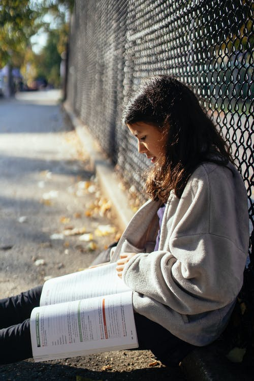 Side view concentrated teenage schoolgirl in loose sweater reading textbook while sitting on ground near wire net fence on sunny autumn day