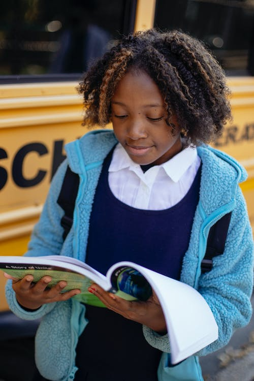 Positive black girl reading textbook near school bus
