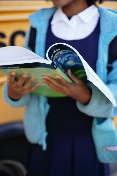 Crop unrecognizable schoolgirl reading textbook while standing near yellow school bus on sunny autumn day