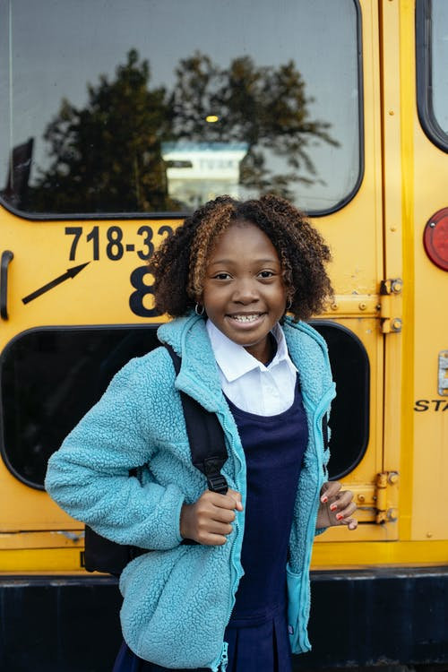 Cheerful African American girl with curly hair standing with backpack near yellow school bus and looking at camera with smile