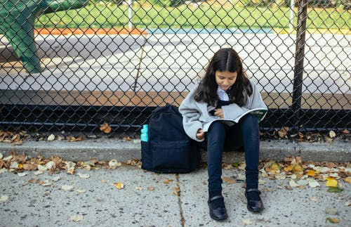 Full body concentrated schoolgirl in warm sweater reading topic in textbook while sitting on ground near net fence in autumn park