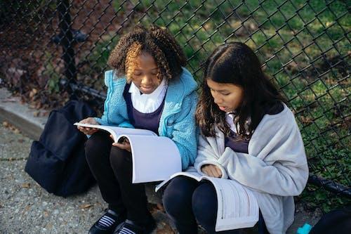 Focused diverse schoolgirls reading textbooks in park