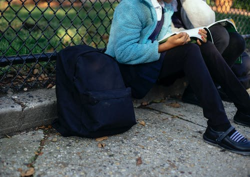 Crop unrecognizable schoolgirls reading textbook in park