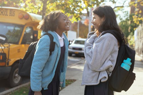 Side view happy multiracial schoolgirls in warm jackets with backpacks standing on street near school bus and talking while looking at each other with smile