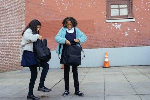 Multiethnische Schulmädchen, Die Außerhalb Der Schule Stehen Und Rucksäcke Schließen