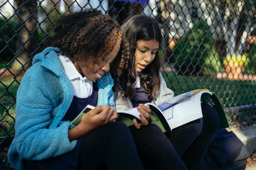 Focused multiracial girls pupils reading textbooks while sitting together on ground near net fence in autumn park