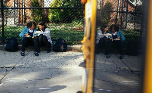 Full body happy multiracial girls classmates with textbooks sitting together on ground near school fence and chatting on sunny autumn weather