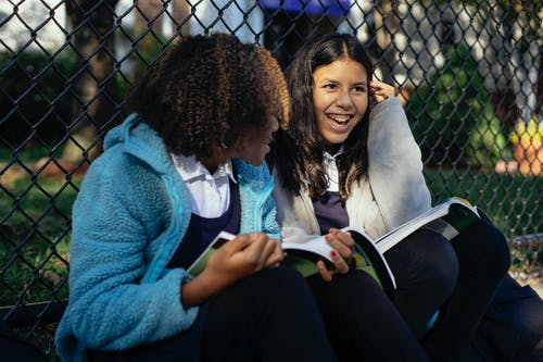 Joyful multiethnic schoolgirls sitting with textbooks in autumn park