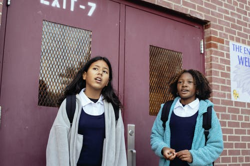 Positive multiracial girls classmates in warm jackets standing together near masonry school wall and looking away