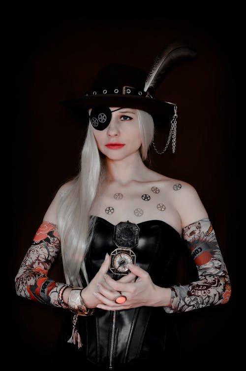 Serious female with eye patch and hat wearing pirate carnival outfit standing with compass against black background