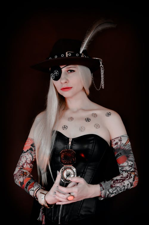 Creative female wearing hat and black corset with pirate eye patch standing with compass and looking at camera