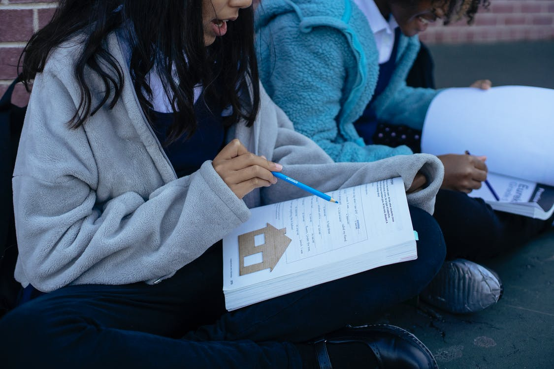 Young diverse pupils studying lesson together while sitting in yard