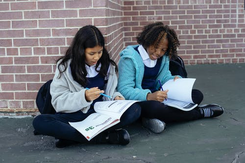 Multiethnic pupils reading textbooks and doing exercises