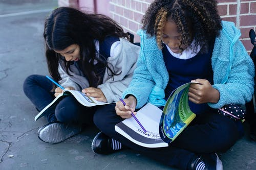Multiracial children doing exercises with pencil in textbooks