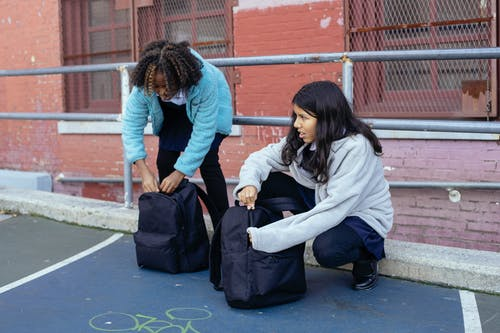 Adorable multiracial children touching backpacks while talking about education near old building of school