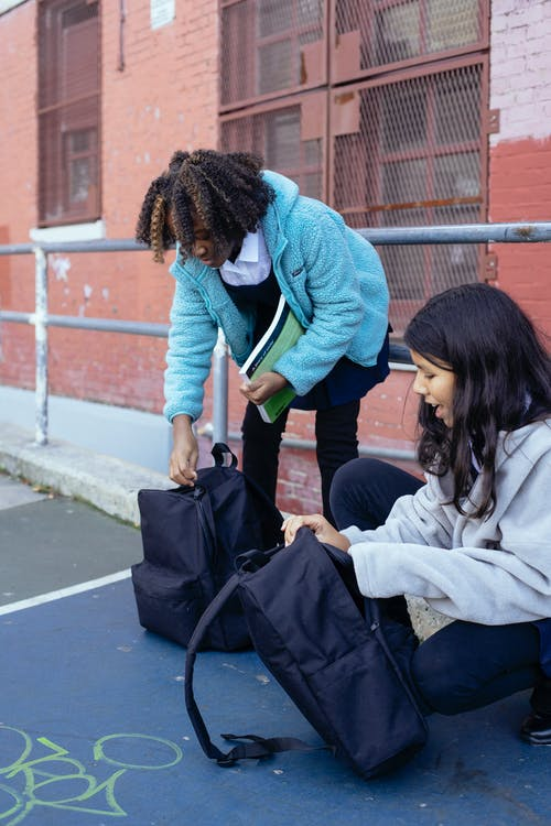 Siswi Multietnis Yang Menggemaskan Dan Ceria Sedang Mempersiapkan Buku Teks Untuk Pembelajaran
