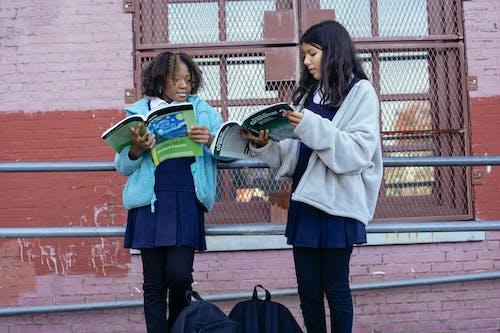 Serious multiracial girls doing homework with textbooks near school