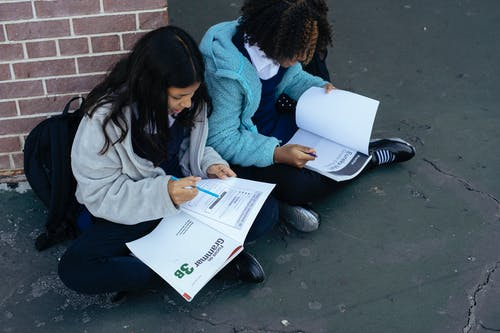 From above of adorable diligent pupils learning and reading textbooks while sitting near brick wall