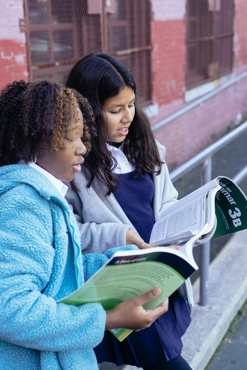 Smart diverse girls talking and reading textbooks together