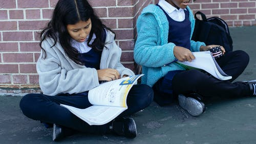 Clever multiracial pupils looking at textbooks and discussing homework together while sitting near brick building