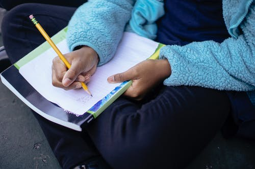 Clever diligent ethnic child doing homework on sheet of paper