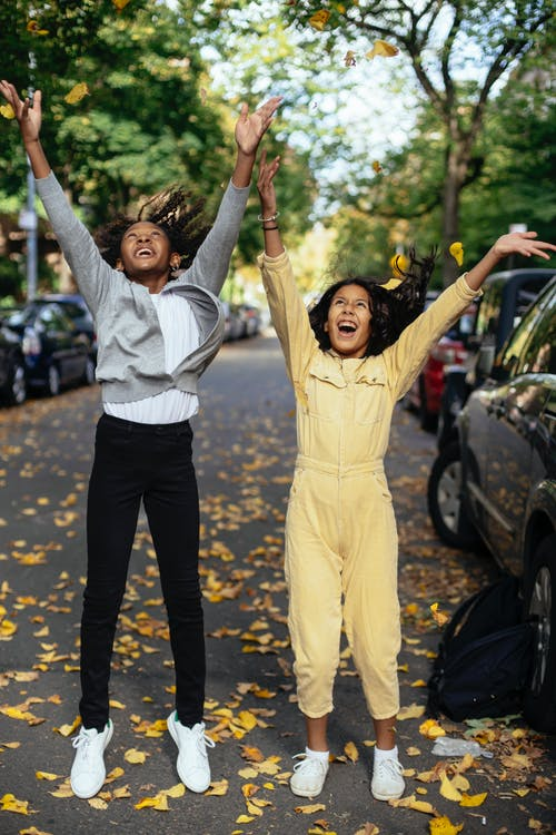 Full body of cheerful cute multiethnic girls with raised hands looking up and screaming on street with autumn leaves