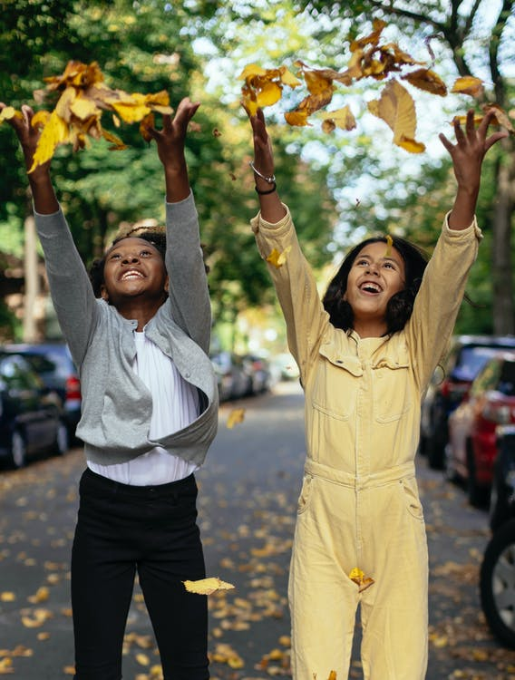 Cheerful glad diverse girls in casual outfit smiling and throwing leaves on street