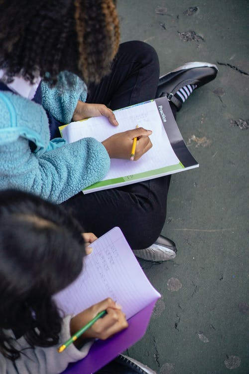 Diligent multiethnic girls writing on sheet of paper