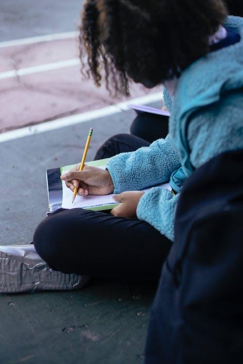 Black girl writing homework on paper