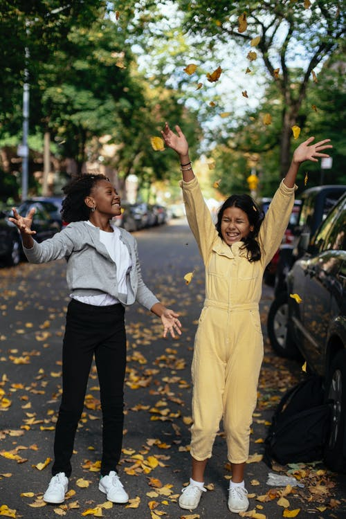Vrolijke Diverse Grappige Meisjes Spelen Met Herfstbladeren Op Straat