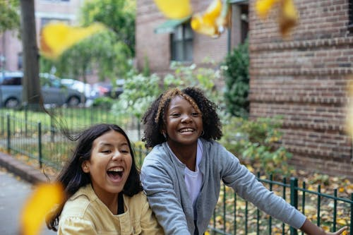 Cheerful diverse girls with smiling and laughing while throwing leaves