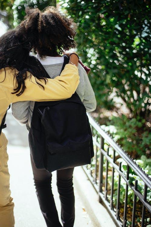 Girls hugging and walking on street