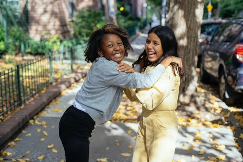 Cheerful glad multiracial girls smiling and laughing while playing