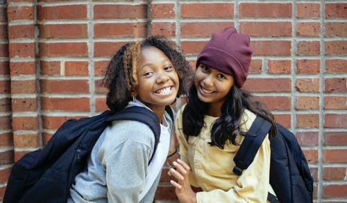 Happy black schoolkid with Afro hairstyle standing close to content best Hispanic friend while looking at camera on street