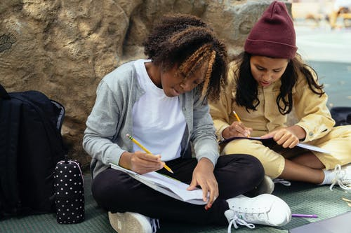 Focused multiracial schoolkids taking notes in copybooks while studying with crossed legs on urban pavement