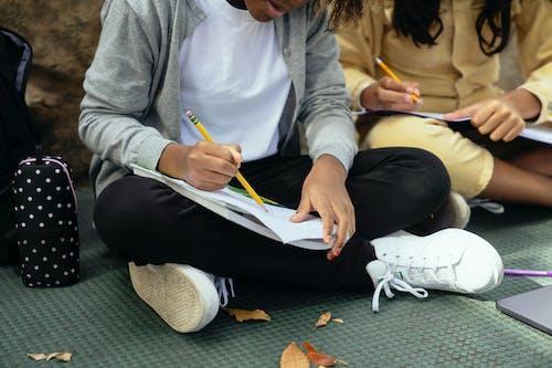 Crop diverse schoolchildren doing homework on urban pavement