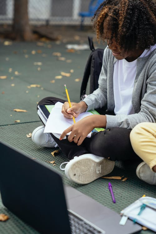 Focused African American schoolchild taking notes on paper while doing homework with crossed legs near netbook and unrecognizable friend on pavement