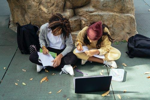 Unrecognizable multiracial schoolgirls writing in workbook on urban pavement