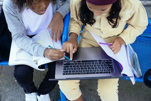 Crop multiethnic schoolgirls with laptop and workbooks doing homework outdoors